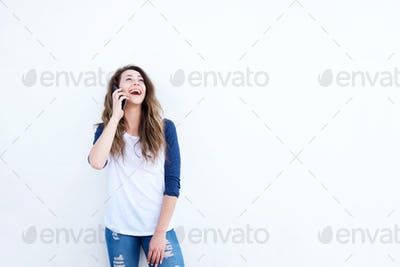 happy young woman talking on cellphone by white wall