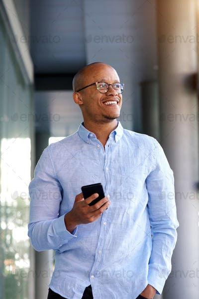 smart looking african businessman walking with cellphone