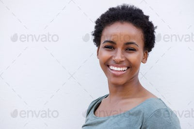 Close up beautiful young black woman smiling against white background