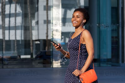 smiling young black woman walking with earphones and mobile phone