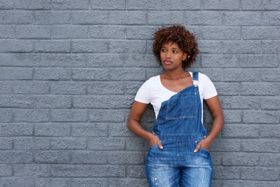 african woman in dungarees by gray wall