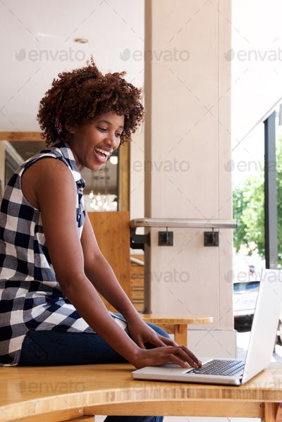 african woman smiling with laptop computer
