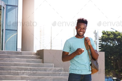 smiling african student holding cellphone and bag on campus