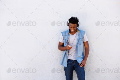 smiling black man leaning against wall with smart phone and headphones