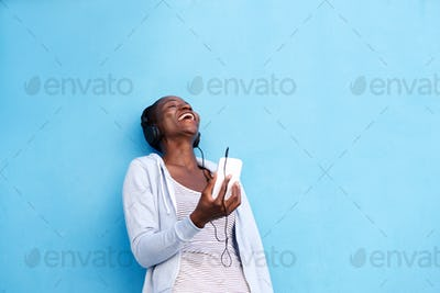 happy woman with smart phone and headphones by blue wall