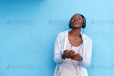laughing woman with smart phone and headphones by blue wall