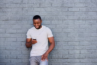 smiling man with mobile phone leaning on brick wall