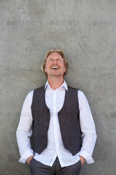 happy middle aged man laughing and looking up