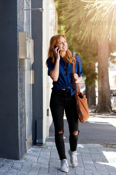 smiling young woman talking on mobile phone with purse
