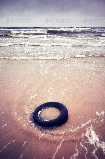 Old black rubber tire left on a beach.