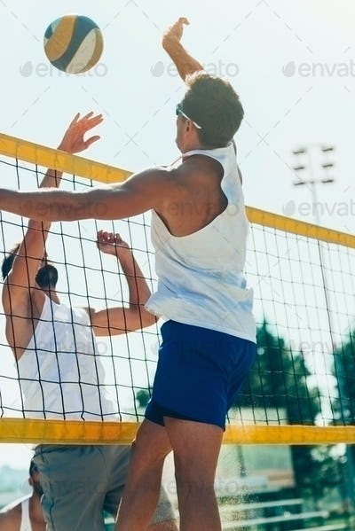 Male beach volleyball players jupming to hit the ball