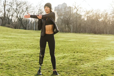 Image of beautiful handicapped sportswoman in tracksuit with pro