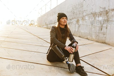 Photo of athletic disabled girl with prosthetic leg in sportswea