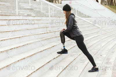 Image of disabled running girl with prosthetic leg in sportswear