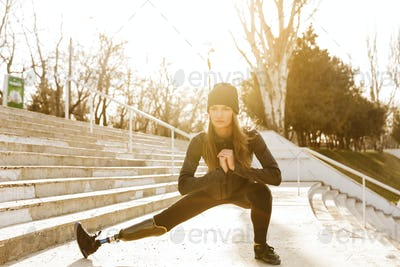 Image of disabled running girl in sportswear, doing sit ups and