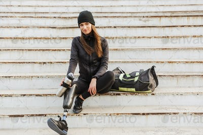 Photo of smiling handicapped woman in sportswear with prosthetic