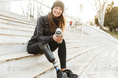 Strong willed handicapped woman in black tracksuit with prosthet