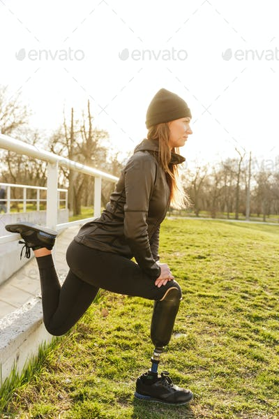 Photo of disabled running woman in sportswear, squatting and str