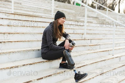 Photo of atlethic disabled woman in sportswear with prosthetic l