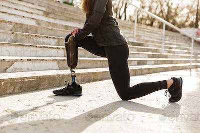 Cropped image of disabled sporty woman in tracksuit, doing sport