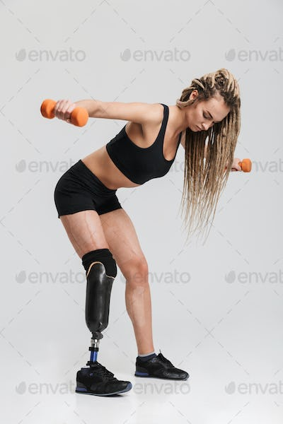 Healthy young disabled sportswoman make exercises with dumbbells.