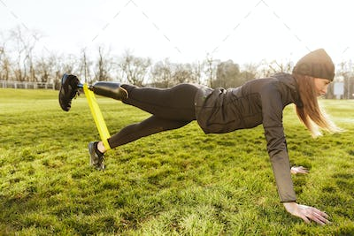 Image of sporty handicapped woman in black tracksuit, warming up