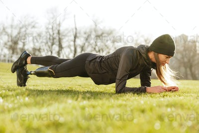 Image of athletic handicapped woman in black tracksuit, doing pl