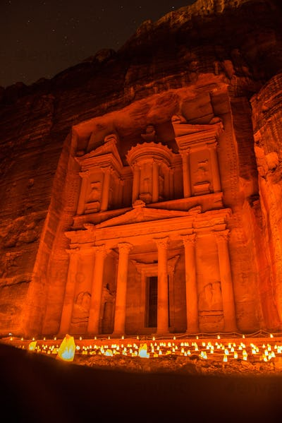 Petra by night, Jordan. The Treasury and the Siq canyon illuminated by candle lights