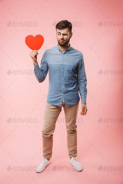 Full length of a confused young man holding red heart