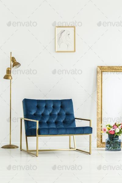 A luxurious, navy blue armchair, golden elements,framed art and