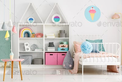 White kid's room interior with a single bed, rainbow on the shel