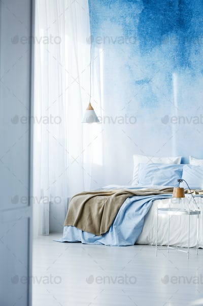 Bright bedroom interior with double bed, beige blanket and ombre