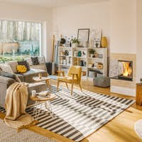 Blanket thrown on grey corner sofa in white living room interior