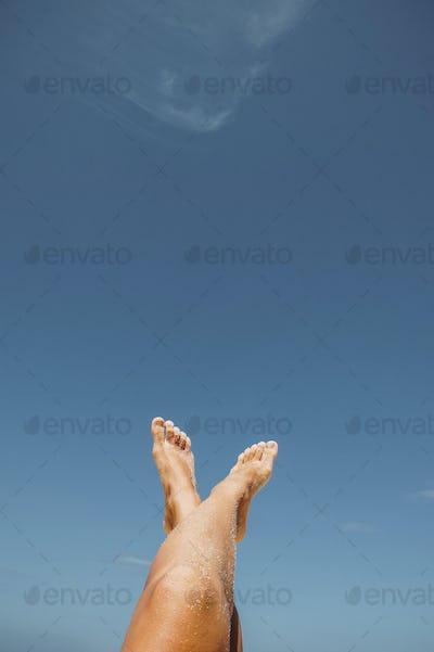 female feet in white sand