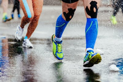 legs runner in compression socks and kinesiology tape