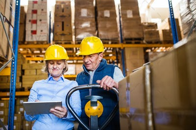 Senior woman manager and man worker with tablet working in a warehouse.