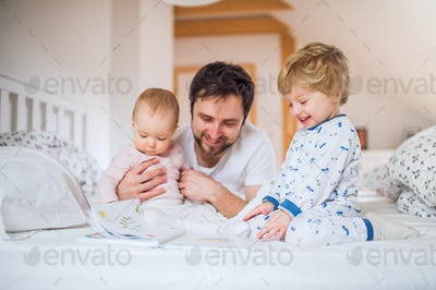 Father with toddler children reading on bed at home at bedtime.