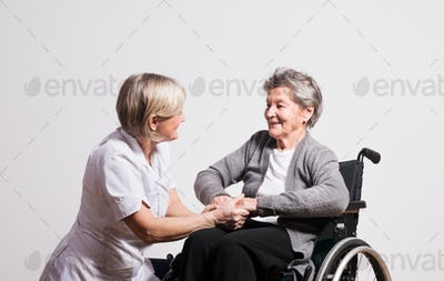 Studio portrait of a senior nurse and an elderly woman in wheelchair.