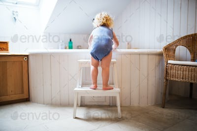 Toddler boy in a dangerous situation in the bathroom.