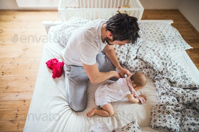 Father with a toddler girl on bed at home at bedtime.