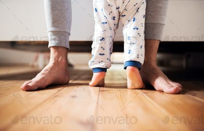 Legs of father and a toddler boy standing on the floor in bedroom at home.