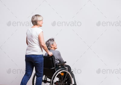 Studio portrait of a senior woman in wheelchair with a carer.