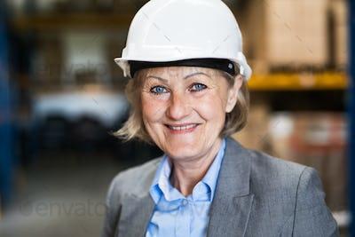 Senior woman warehouse manager or supervisor with white helmet.