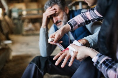 A woman bandaging a hand of a man worker after accident in carpentry workshop.
