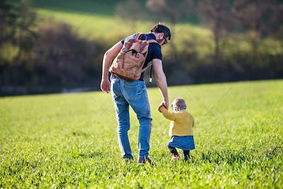 A father with his toddler daughter on a walk outside in spring nature.