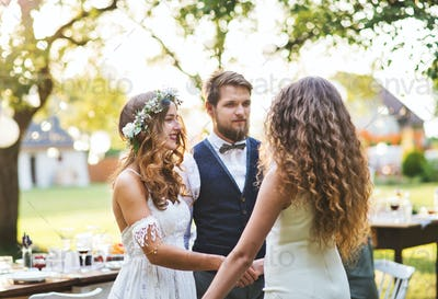 Young girl congratulating bride and groom at wedding reception in the backyard.