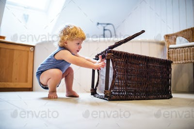 Toddler boy with a laundry basket in the bathroom.