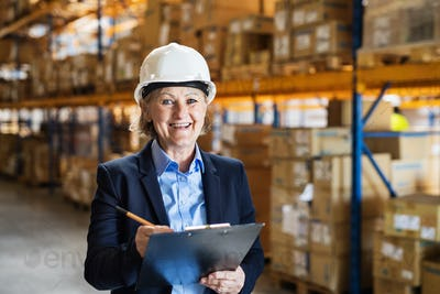 Senior woman warehouse manager or supervisor with white helmet and clipboard.