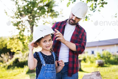 Father with a small daughter having fun with helmets in garden. Spring nature.