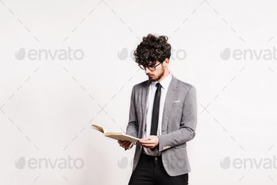 Portrait of a young man with a book in a studio on a white background.